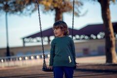 Счастливый белокурый мальчик играя в парке на цепном качании стоковое фото rf