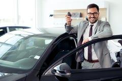 Счастливый бизнесмен держа ключи к ее новому автомобилю на дилерских полномочиях Стоковые Фото