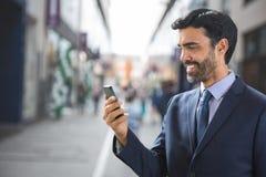 Счастливый бизнесмен используя телефон против предпосылки улицы Стоковые Изображения RF