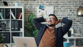 Счастливый бизнесмен ослабляя в офисе наслаждаясь сидеть перерыва работы усмехаясь сток-видео