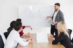 счастливый бизнесмен усмехаясь и делая представление на whiteboard и указывая на диаграмму босс представляя стратегию  стоковое изображение