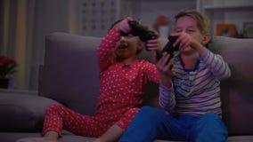 Счастливый брат и сестра играя видеоигру вечером сидя софа, наркомания видеоматериал