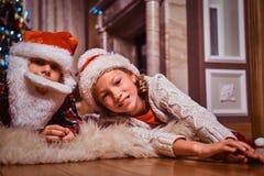Счастливый брат и сестра нося шляпу santa лежа на ковре меха около рождественской елки дома стоковые изображения rf