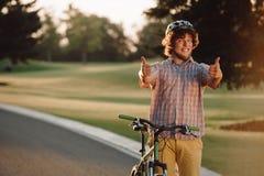 Счастливый велосипедист давая 2 большого пальца руки вверх outdoors Стоковые Фото