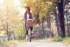 Счастливый велосипед велосипеда катания женщины в парке осени падения Стоковая Фотография