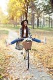 Счастливый велосипед велосипеда катания женщины в парке осени падения Стоковое Фото