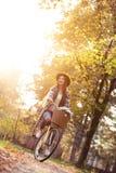 Счастливый велосипед велосипеда катания женщины в парке осени падения Стоковое Изображение RF