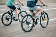 Счастливый велосипед катания пар outdoors на лете от задней части Стоковое фото RF