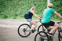 Счастливый велосипед катания пар outdoors на лете от задней части Стоковая Фотография