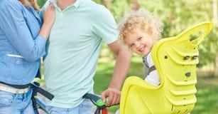 Счастливый велосипед катания семьи на парке Стоковое Изображение RF