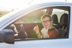Счастливый владелец автомобиля показывает большие пальцы руки вверх внутри его нового автомобиля Стоковое Фото