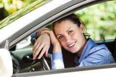 Счастливый водитель девушки усмехаясь к вам стоковое фото