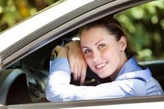 Счастливый водитель девушки усмехаясь к вам стоковая фотография