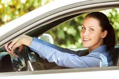 Счастливый водитель девушки усмехаясь к вам стоковое фото rf