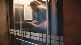 Счастливый вскользь кавказский мужской фрилансер ехать прозрачный стеклянный лифт, дверь раскрывает и он идет вне используя smart акции видеоматериалы