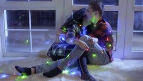 Счастливый в гирлянде влюбленностей украшенной парами красочной ослабьте около окна на поле видеоматериал