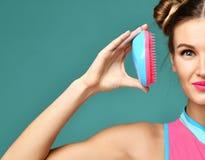 Счастливый глаз конца женщины брюнет моды с красочной розовой голубой популярной щеткой гребня волос Стоковые Фотографии RF