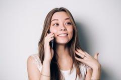 Счастливый говорить телефона женщины Сторона при зубастая улыбка, изолированная над белизной стоковое фото rf