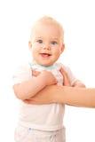 Счастливый голубоглазый младенец стоя с рукоятками матери Стоковое Изображение RF