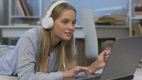 Счастливый девочка-подросток в наушниках слушая к музыке и беседуя с друзьями сток-видео