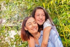 Счастливый девочка-подросток давая ее объятие матери назад стоковая фотография rf