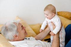 Счастливый дед держа прелестный внука ребёнка на оружиях Стоковая Фотография