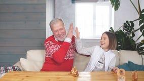 Счастливый дед играя игры с его внучкой внутри помещения сток-видео