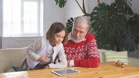 Счастливый дед играя игры с его внучкой внутри помещения акции видеоматериалы