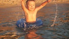 Счастливый делать мальчика брызгает в воде Ребенок имея потеху в море на заходе солнца сток-видео