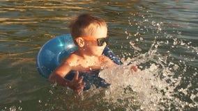 Счастливый делать мальчика брызгает в воде Ребенок имея потеху в море на заходе солнца видеоматериал