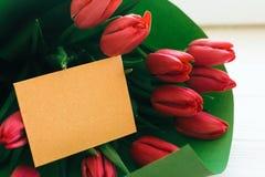 Счастливый день матерей Красивый красный букет тюльпанов в зеленой книге и карте ремесла с космосом для текста на белой деревянно стоковые фотографии rf