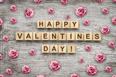 Счастливый день, надпись на деревянных кубах и бутоны Валентайн розовых роз на серой деревянной предпосылке празднично стоковые фото