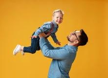 Счастливый День отца! милый папа и сын обнимая на желтой предпосылке стоковые изображения