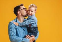 Счастливый День отца! милый папа и сын обнимая на желтой предпосылке стоковая фотография rf