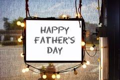Счастливый день отцов написанный на знаке смертной казни через повешение окруженном партией освещает в окне магазина с полу-прозр Стоковое Изображение