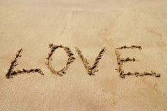 Счастливый день Святого Валентина, ЛЮБОВЬ помечая буквами на пляже с волной и солнечный свет стоковое фото