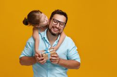 Счастливый день ` s отца! милый папа и дочь обнимая на задней части желтого цвета Стоковое Фото