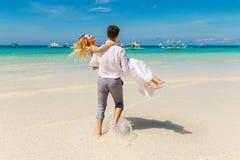 Счастливый жених и невеста имея потеху на тропическом пляже тропическо стоковое изображение
