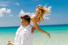 Счастливый жених и невеста имея потеху на тропическом пляже тропическо стоковое фото