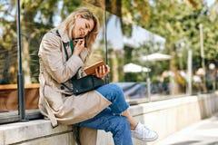 Счастливый женский говорить на мобильном телефоне, читая некоторые извещения в тетради стоковые фотографии rf