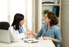 Счастливый женский доктор и молодой усмехаясь пациент женщины тряся руки в офисе клиники стоковые фото