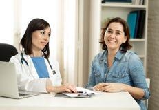 Счастливый женский доктор и пациент детенышей удовлетворенный усмехаясь имея консультацию в офисе клиники стоковые фотографии rf