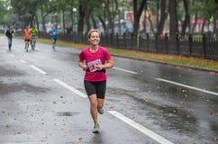 Счастливый женский участник бежать на улице города Dnipro во время 42 км расстоянии марафона ATB Dnipro стоковые фото