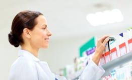 Счастливый женский apothecary с лекарством на фармации стоковые изображения rf
