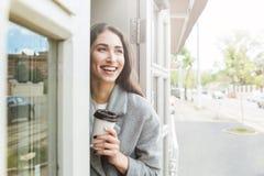Счастливый жизнерадостный усмехаясь кофе взятия удерживания девушки отсутствующий Стоковое Фото