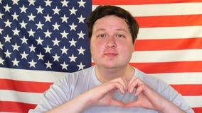 Счастливый жирный человек в любов делая сердце с пальцами и усмехаясь на предпосылке флага США видеоматериал