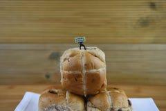 Счастливый знак пасхи держал миниатюрным figurine персоны стоя на некоторых свежих горячих перекрестных плюшках Стоковые Фото