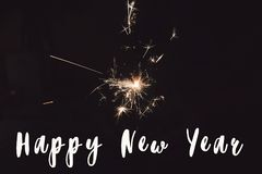Счастливый знак текста Нового Года, рука держа горящий свет Бенгалии фейерверка бенгальского огня Космос для Стоковые Фото
