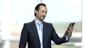 Счастливый зрелый бизнесмен имея видео-чат акции видеоматериалы