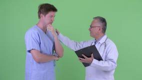 Счастливый зрелый японский доктор человека с пациентом молодого человека получая хорошие новости совместно сток-видео